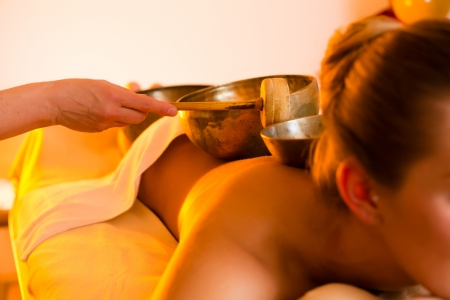 Woman in wellness and spa setting having a singing bowl massage therapy Stock Photo - 17109071