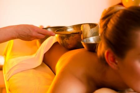 Woman in Wellness-und Spa-Einstellung mit einer Klangschale Massage-Therapie