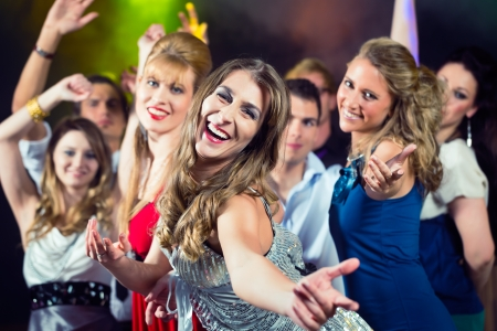 prom dress: Young people dancing in club or disco and have party; the girls and boys, friends, having fun