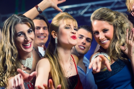 Young people dancing in club or disco and have party; the girls and boys, friends, having fun Stock Photo - 17108989