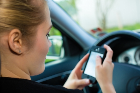 autos: Young woman, in car with mobile phone , checking her text message or her navigation