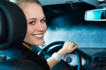 autos: Young woman drives car in wash station cleaning the auto