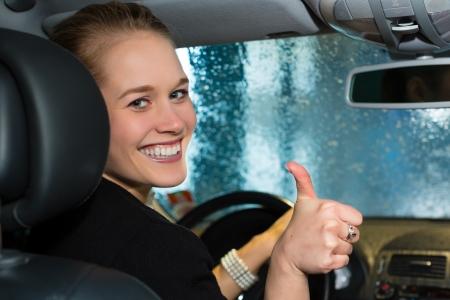 cleaning car: Mujer joven conduce coche en la estaci�n de lavado de auto limpieza
