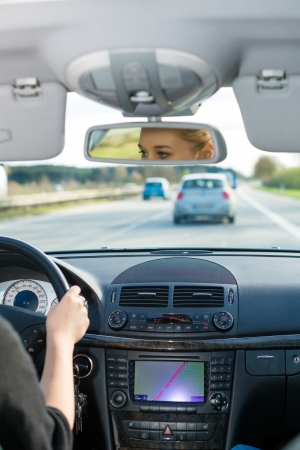 autobahn: Young woman driving by car on the autobahn, view from inside the auto