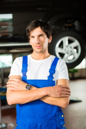 car hoist: Auto mechanic standing in his workshop in front of a car on a hoist