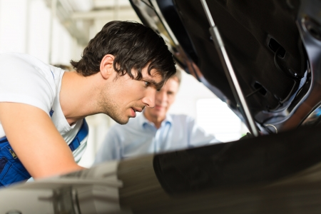 Mature man - client - and young mechanic are looking beneath a hood with a lamp Stock Photo - 17109082