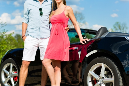 cabriolet: Young hip couple - man and woman - with cabriolet convertible car in summer on a day trip Stock Photo