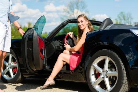 convertible car: Young hip couple - man and woman - with cabriolet convertible car in summer on a day trip Stock Photo