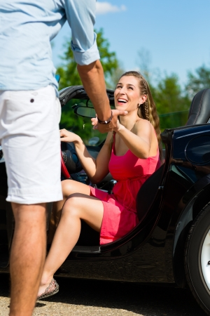 get out: Young hip couple - man and woman - with cabriolet convertible car in summer on a day trip Stock Photo