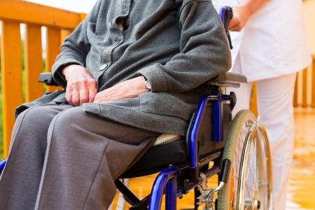 ancianos caminando: Enfermera joven y mujer mayor en una silla de ruedas a dar un paseo