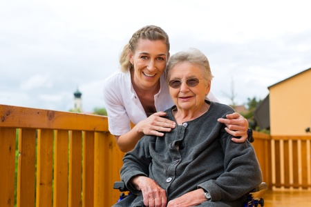 oldage: Young nurse and female senior in a wheel chair going for a walk Stock Photo