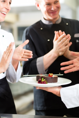 commercial kitchen: Chef team in restaurant kitchen with dessert, the colleagues applauding because the dish works great Stock Photo