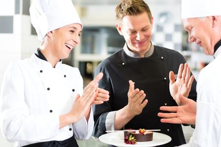 Chef-kok team in keuken van het restaurant met dessert, de collega's applaudisseren omdat de schotel werkt prima Stockfoto