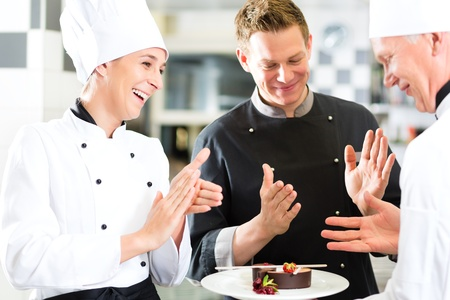 chefs: Chef team in restaurant kitchen with dessert, the colleagues applauding because the dish works great Stock Photo