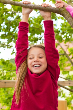 romp: Happy child playing in the garden hanging on the tree Stock Photo