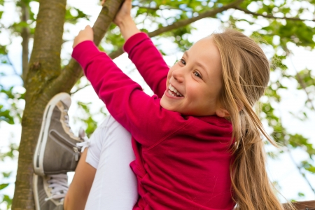 romp: Happy child playing in the garden climbing on the tree Stock Photo