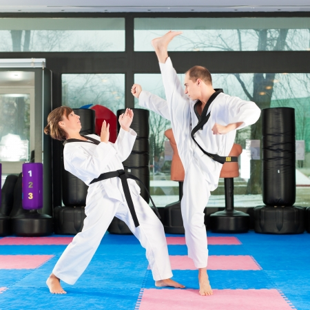 tae: People in a gym in martial arts training exercising Taekwondo, both have a black belt