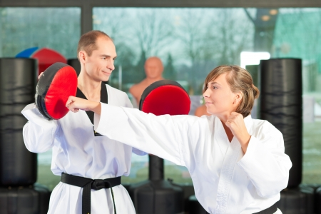 martial art: People in a gym in martial arts training exercising Taekwondo, both have a black belt
