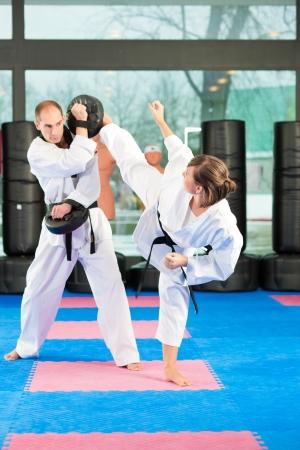martial arts: Las personas en un gimnasio de entrenamiento de artes marciales Taekwondo ejercicio, ambos tienen un cintur�n negro
