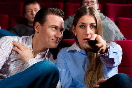 Couple and other people, probably friends, in cinema watching a movie, they try to switch to another program that is not possible in a cinema Stock Photo - 17264859