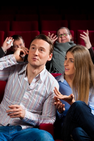 Couple and other people, probably friends, in cinema watching a movie, one is making a phone call and bothering the others  photo
