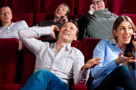 comedic: Couple and other people, probably friends, in cinema watching a movie, everybody is making a phone call, it seems to be a boring movie