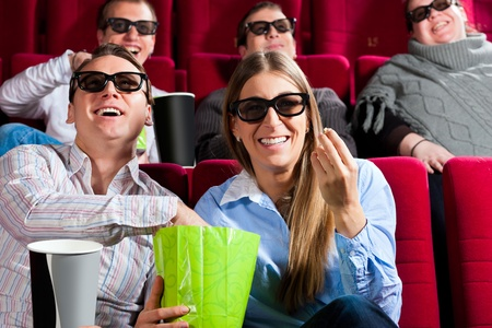 Couple in cinema theater watching a movie in 3D with glasses and popcorn photo