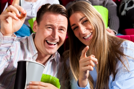 Couple in cinema watching a movie, it seems to be a funny movie photo