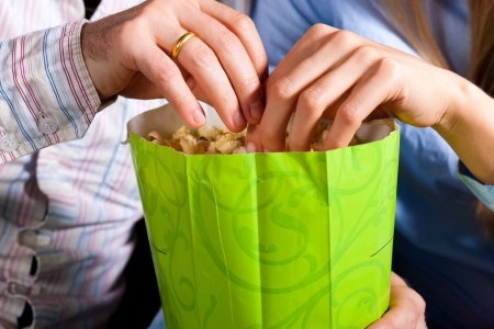 Couple in cinema theater watching a movie, they eating popcorn, close-up Stock Photo - 17249324