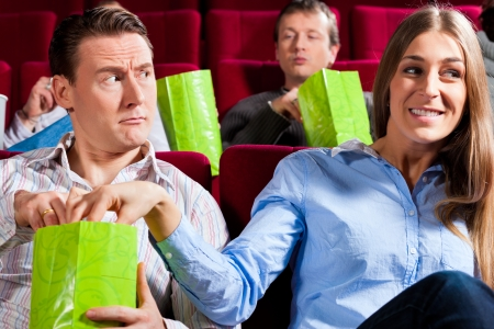 Couple in cinema theater watching a movie, they eating popcorn photo