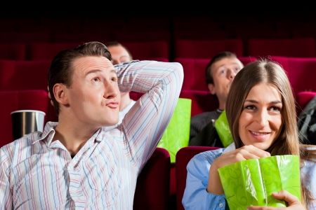Couple in cinema watching a movie, they eating popcorn photo