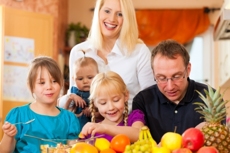 Family (mother, father and children) with lots of fruits for breakfast food, this is healthy nutrition photo