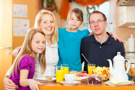 Family eating breakfast in the kitchen of their house photo