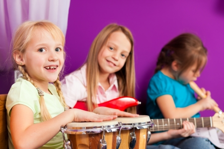 making music: Children - sisters - making music at home, they are practicing playing guitar, bongo and flute as instruments