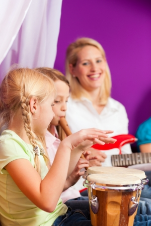 making music: Family - Children and mother - making music, at home, they are practicing playing guitar, bongo and flute as instruments Stock Photo