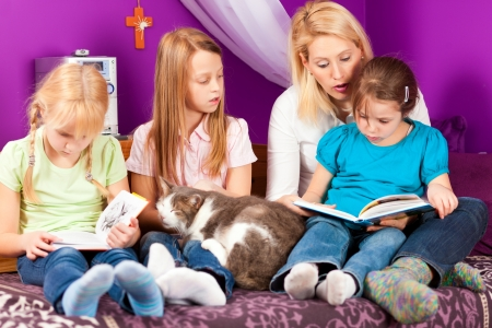 nanny: Happy family - mother is reading a book, she and the children are sitting in a kids room Stock Photo