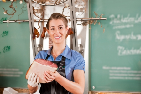 Portrait of smiling female butcher with raw meat photo