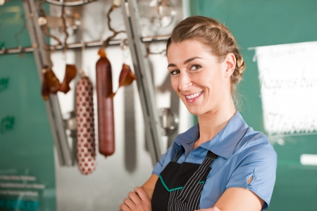 Portrait of pretty female butcher smiling at butchery photo