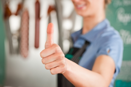 Closeup of female butcher showing thumbs up sign Stock Photo - 17249306