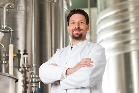 brewer: Brewer pie en su f�brica de cerveza en frente de un fermentador de cobre inoxidable