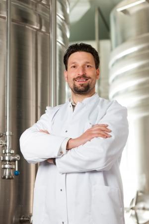 brewer: Brewer pie en su f�brica de cerveza en frente de un fermentador de acero inoxidable