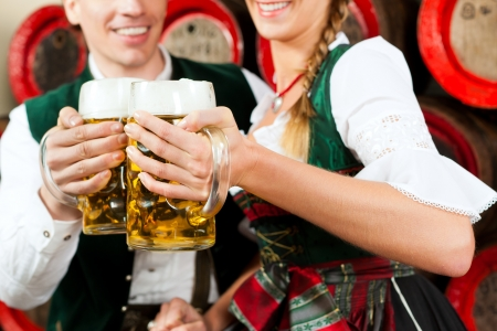 tracht: Young couple, man and woman, in traditional Bavarian Tracht drinking beer in a brewery in front of beer barrels