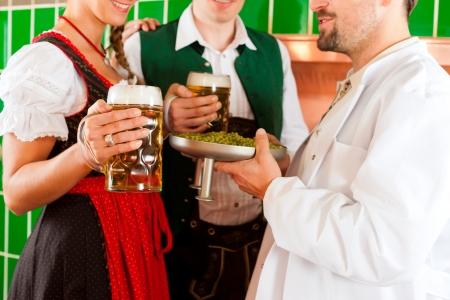 brewer: Hombre y mujer en Tracht b�varo con la cerveza masculina, el l�pulo y la cerveza stein en cervecer�a Foto de archivo