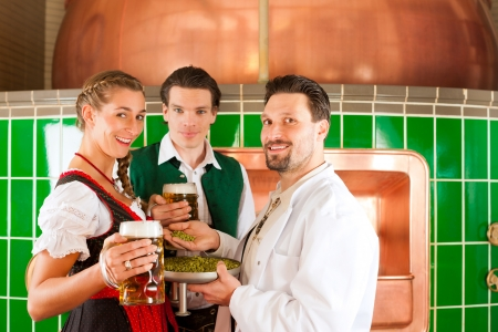 Man and woman in Bavarian Tracht with male brewer, hops and beer stein in brewery photo