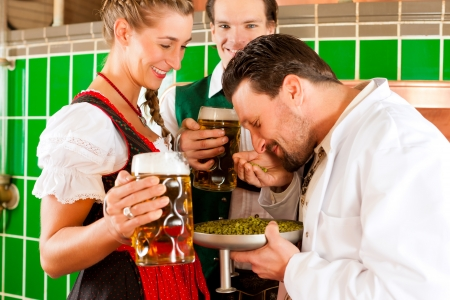steins: Man and woman in Bavarian Tracht with male brewer, hops and beer stein in brewery