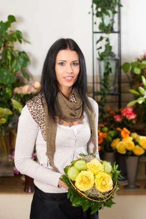 Female florist in flower shop or nursery with yellow roses photo