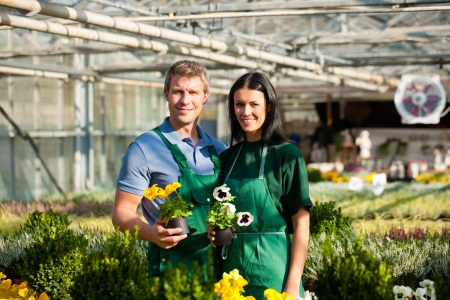Male and female florist or gardener in flower shop or nursery photo