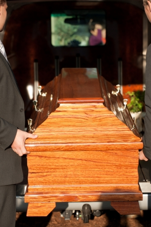 funeral parlor: Dolor - Funeral with coffin on a cemetery, the casket carried by coffin bearer Stock Photo