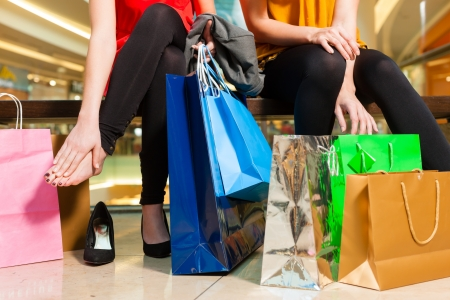 Two female friends with shopping bags having fun while shopping in a mall, the feet hurt already Stock Photo - 17324827
