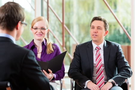 collaborating: Man having an interview with manager and partner employment job candidate hiring resume CEO work business